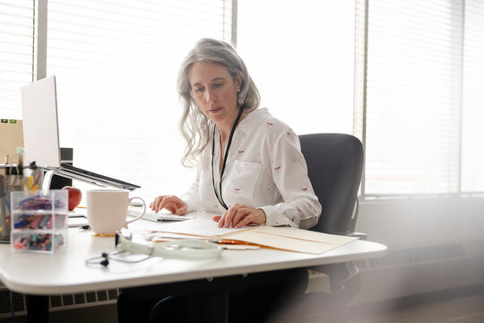 Female doctor reviewing medical chart in clinic office