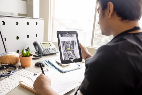 Male doctor reviewing digital xray on digital tablet in clinic office