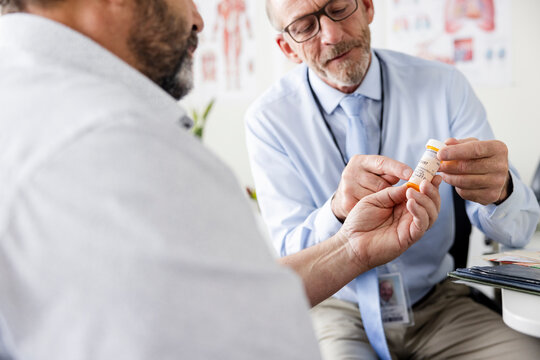 Male doctor prescribing medication to patient in clinic