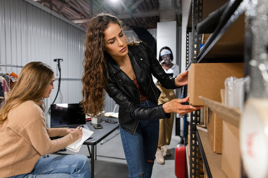 Female entrepreneurs with boxes in storage facility