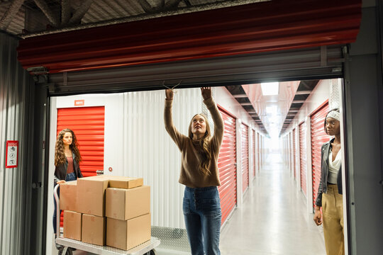 Women with cardboard boxes opening storage facility locker
