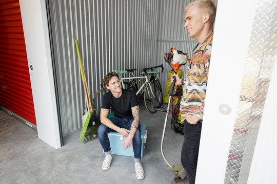 Young men talking in storage facility locker