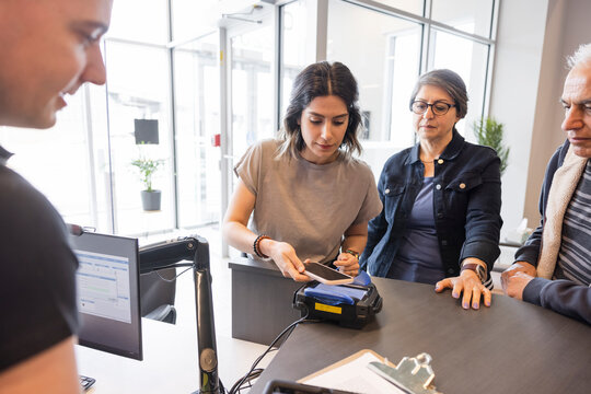 Woman with smart phone paying worker at storage facility front desk