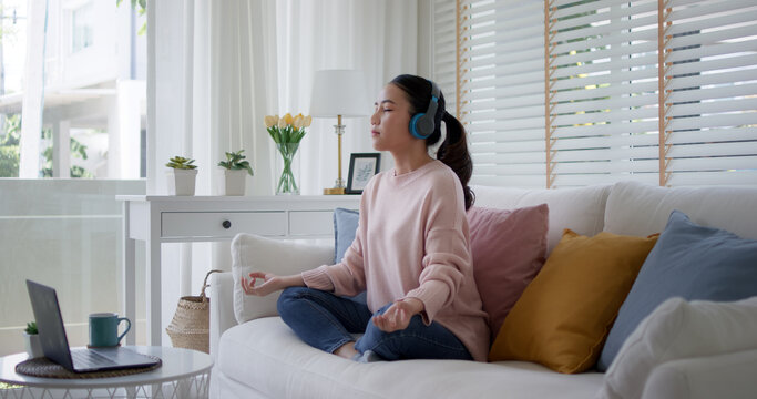 Young asia people teenage girl close eyes sit on sofa couch at home easy asana lotus pose in yoga app zen online class on internet on break time self relax calm, rest mind and mental health life care.