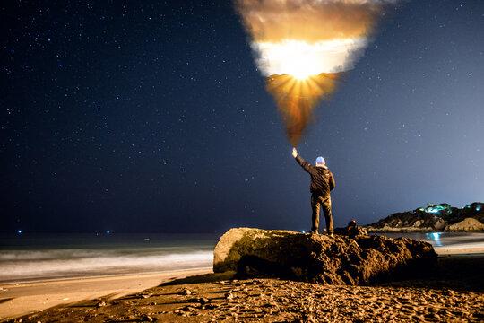 Mann steht am Strand, Portugal, bei Sternenhimmel mit einer Wolke. Sonnenuntergang