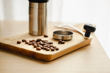 Coffee beans are placed with a coffee grinder on a wooden table.