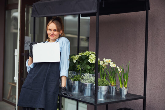 Smiling floriculturist holding a blank outdoor sign in her hands