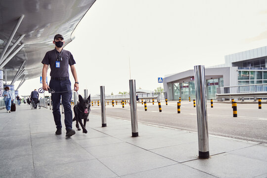 Security officer with detection dog walking outdoors at airport