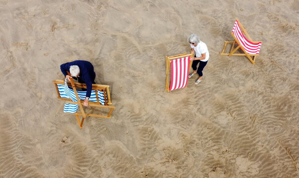 People set up deckchairs on the beach as rental deckchairs returned to the seafront after a 10 year absence in Blackpool