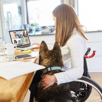 Behinderte Frau bei Videokonferenz am Computer zu Hause