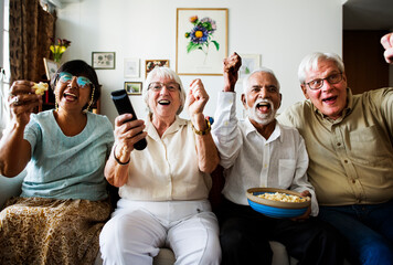 Fototapeta Group of cheerful senior friends sitting and watching TV together obraz