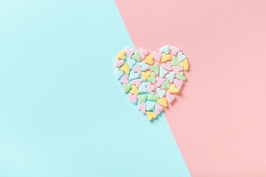 concept of Valentines day greeting with split heart shape from sprinkles over pink and blue background