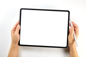 Fototapeta Hand holding a mockup tablet and pencil with blank screen isolated on white obraz