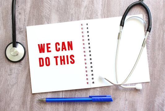 White notebook with red text WE CAN DO THIS and a stethoscope on a gray wooden table.