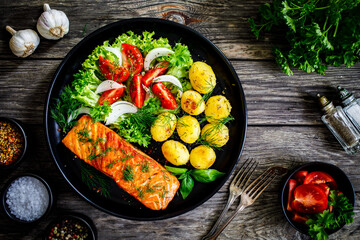 Fototapeta Fried salmon steak with roast potatoes and vegetable salad served on black plate on wooden table  obraz