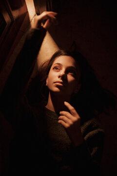 Lonely woman lying in dark room with opened door