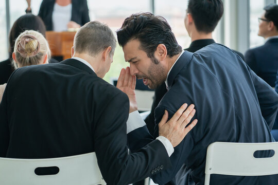 two man whispering while workshop training in business event at seminar room.