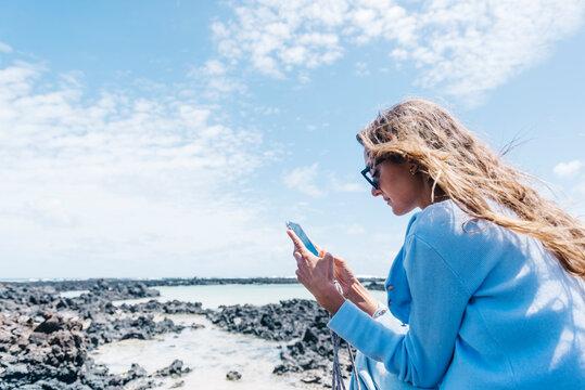 Traveling woman using smartphone on seashore