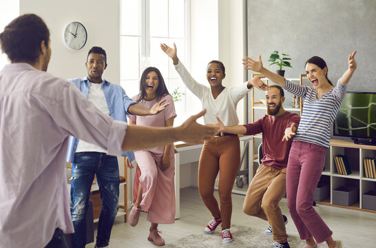 Congratulations: Diverse group of excited young people meet man who's achieved great success. Long time no see: Happy, emotional friends spread arms wide open to hug friend who's finally back home