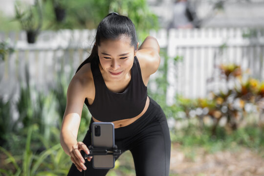Women exercise training with recording video camera on smartphone live streaming for social media.