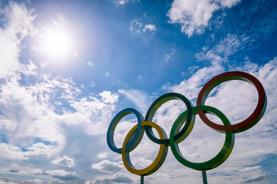 RIO DE JANEIRO - APRIL, 2016: A large set of Olympic Rings stand backlit by bright sun  with light cloud cover in blue sky.