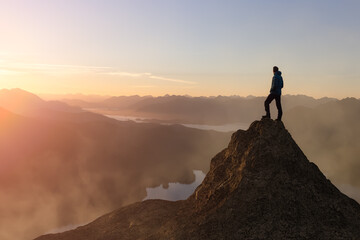 Fototapeta Adventure Composite. Adventurous Adult Man hiking on top of a mountain. Colorful Sunset or Sunrise Sky. 3D Rocky Peak. Aerial Background Landscape from Vancouver Island, British Columbia, Canada. obraz