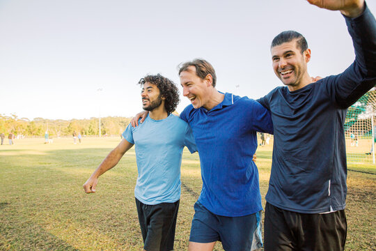 Three men walking together on a soccer field, laughing and smiling, celebrating a win