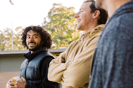 Three men talking and laughing outside one holding a soccer ball
