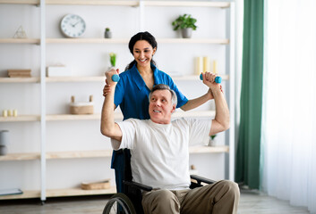 Fototapeta Post-stroke rehabilitation. Female physiotherapist helping elderly male patient in wheelchair to make exercises at home obraz