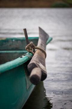 ein altes Holzpaddel oder Ruder von einem grünen Angelboot