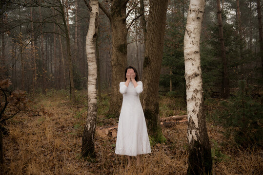Woman in long white dress standing in forest in autumn or winter hiding her face