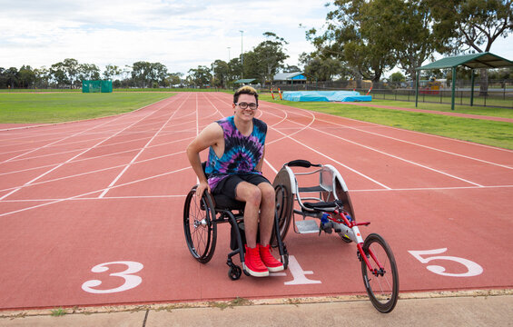 athlete in wheelchair on edge of track with racing wheelchair