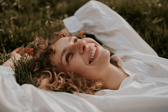 young happy, smiling woman with curls is lying in the grass enjoying spring