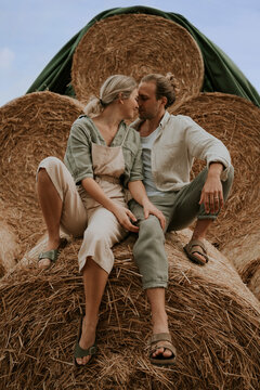 young happy couple kissing on hay bales