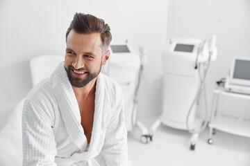 Obraz Smiling man in comfortable bathrobe sits in professional cosmetologycal salon - fototapety do salonu