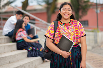 Fototapeta Portrait of an indigenous college student with books in hands in the university. obraz
