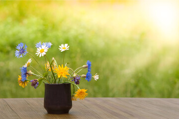Bouquet of wild flowers on a wooden table, photo with blurred background,
