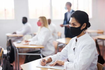 Woman studying in classroom with colleagues medicals in protective face masks for disease...