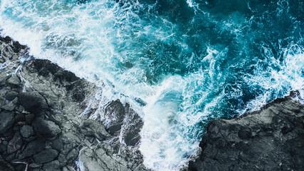 Fototapeta Drone shot of ocean waves clashing into dark rocks obraz