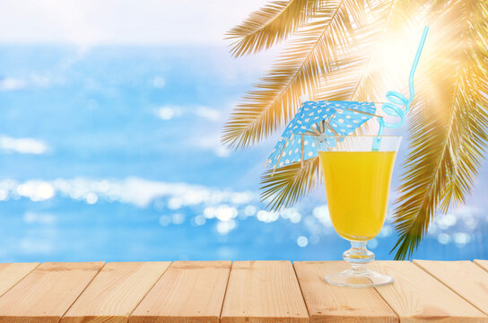 image of tropical and exotic fruit coctail over wooden table infront of sea landscape background