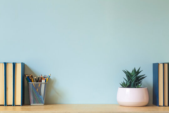 Home office desk table background. Empty wall with wooden table with stationery and books for work or study.