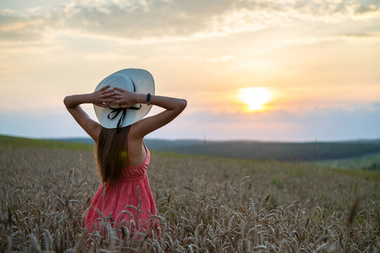 Young happy woman in red summer dress and white straw hat standing on yellow farm field with ripe golden wheat enjoying warm evening.