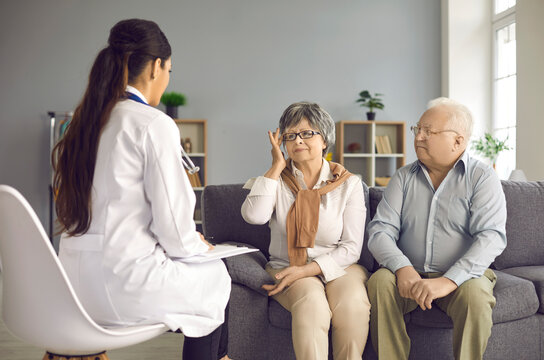 Family doctor listening to senior patients' health concerns and troubles during home visit. Old couple sitting on couch in living-room telling about migraine symptoms and asking for pain relief advice
