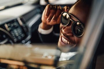 Obraz Stylish black businessman with sunglasses inside of car - fototapety do salonu