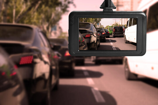 Modern dashboard camera mounted in car, view of road during driving