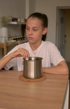 a hobby girl mixes wax in an iron saucepan with a wooden stick for filling a soy candle