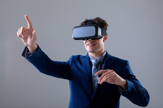 Caucasian businessman wearing vr headset touching virtual interface, isolated on grey background
