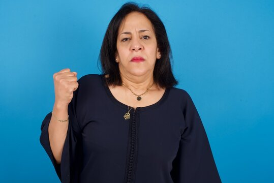 middle aged Arab woman standing against blue background shows fist has annoyed face expression going to revenge or threaten someone makes serious look. I will show you who is boss