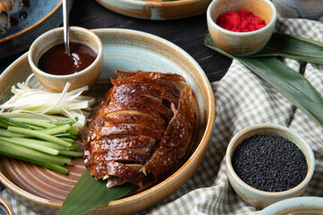 side view of traditional asian food peking duck with cucumbers and sauce on a plate