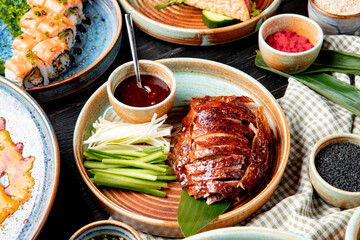 Fototapeta side view of traditional asian food peking duck with cucumbers and sauce on a plate obraz